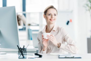 Smiling businesswoman drinking coffee at office