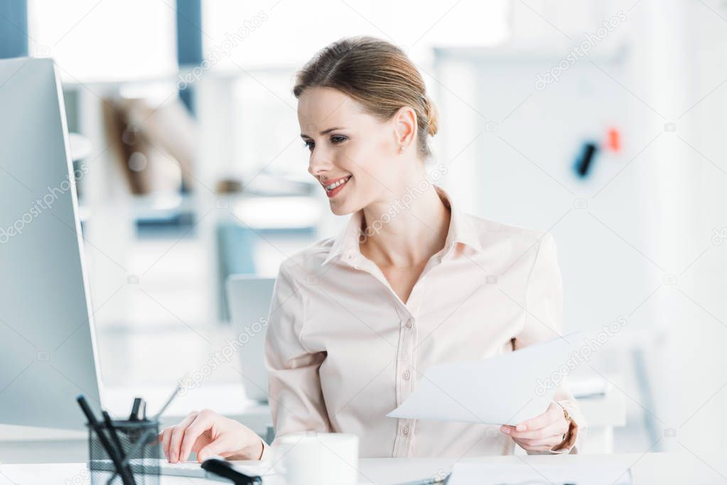 businesswoman working with documents and computer at office