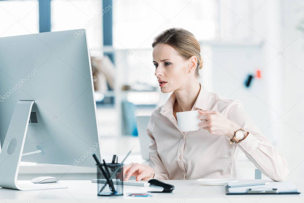 businesswoman working on computer and drinking coffee