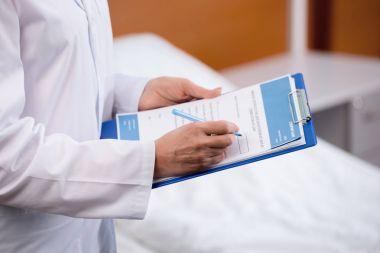 Doctor writing in clipboard