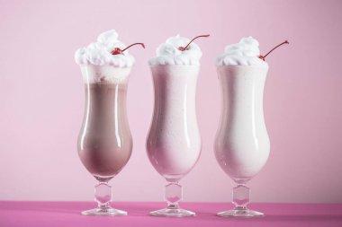 Row of various sweet milkshakes with cherries in glasses on pink surface stock vector