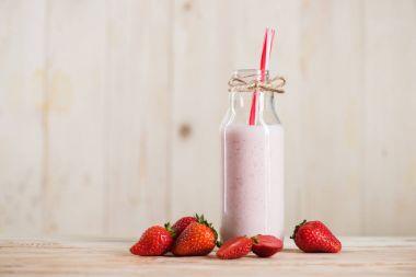 strawberry milkshake with straw in glass