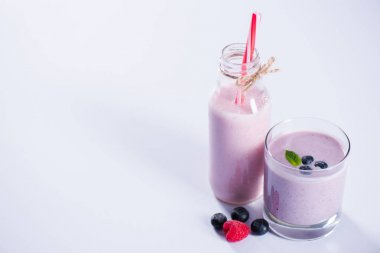 smoothie with blueberries in glass and bottle