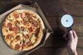 Fotografie Person schneidet Pizza