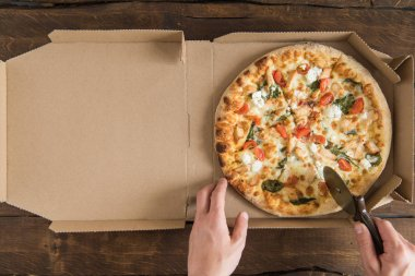 Person cutting pizza