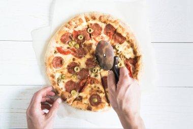 man cutting pizza
