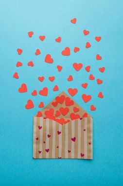 Open envelope full of red hearts for Valentine day on blue surface stock vector