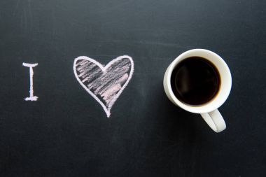 Top view of love heart doodle drawing on chalkboard with cup of coffee stock vector