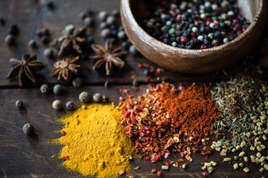 pepper in bowl and spices with herbs on tabletop