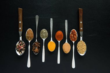 various spices and herbs in metal spoons