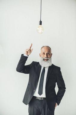 Senior businessman pointing at idea light bulb on light background stock vector