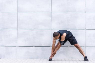 african american runner stretching on street