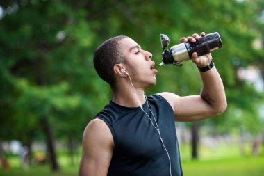 african american sportsman drinking water