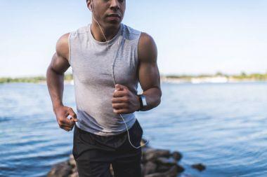 african american sportsman running at riverside