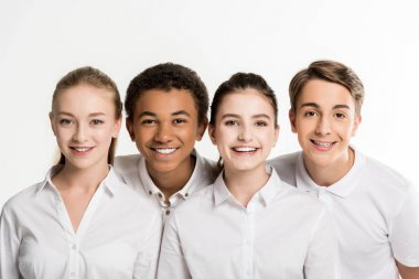 Smiling multiethnic teenagers in white shirts