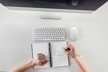student drawing graphic in notebook