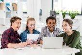multiethnic teenagers using laptop