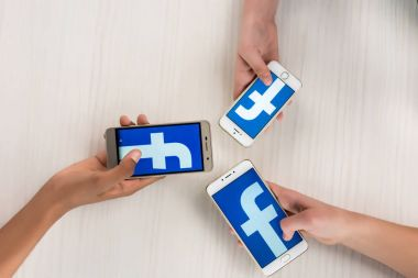Cropped shot of teenagers holding smartphones with facebook logo on screens in hands stock vector