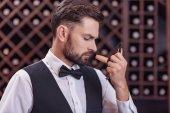 Fotografie sommelier examining smell of wine cork