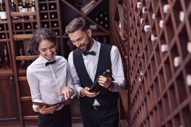 sommeliers choosing wine in cellar