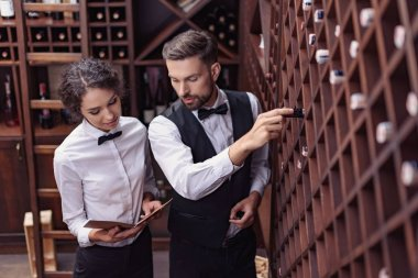 sommeliers choosing wine in cellar