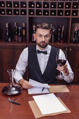 Young handsome man sommelier tasting red wine in cellar stock vector