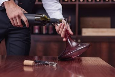 sommelier pouring red wine