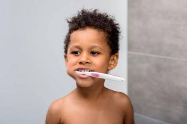 afro kid brushing teeth