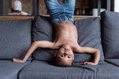 dítě stojící vzhůru nohama na pohovce