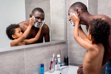 son applying shaving foam on father