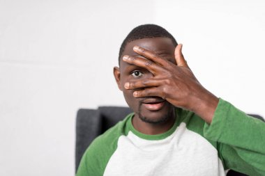 man covering face with hand