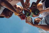 Freunde klirren mit Gläsern und Flaschen
