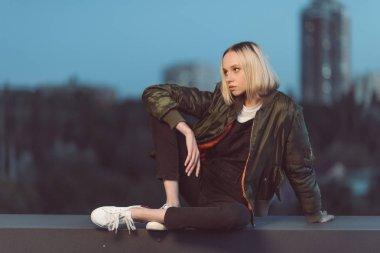 stylish woman sitting outdoors
