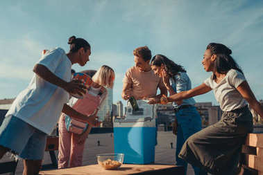 friends with fridge of beer on roof