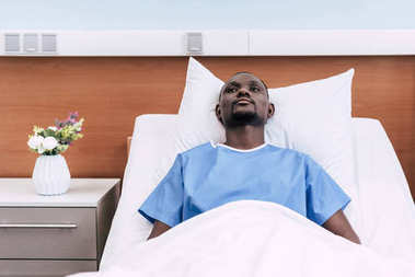 Thoughtful african american man looking away while lying in hospital bed stock vector