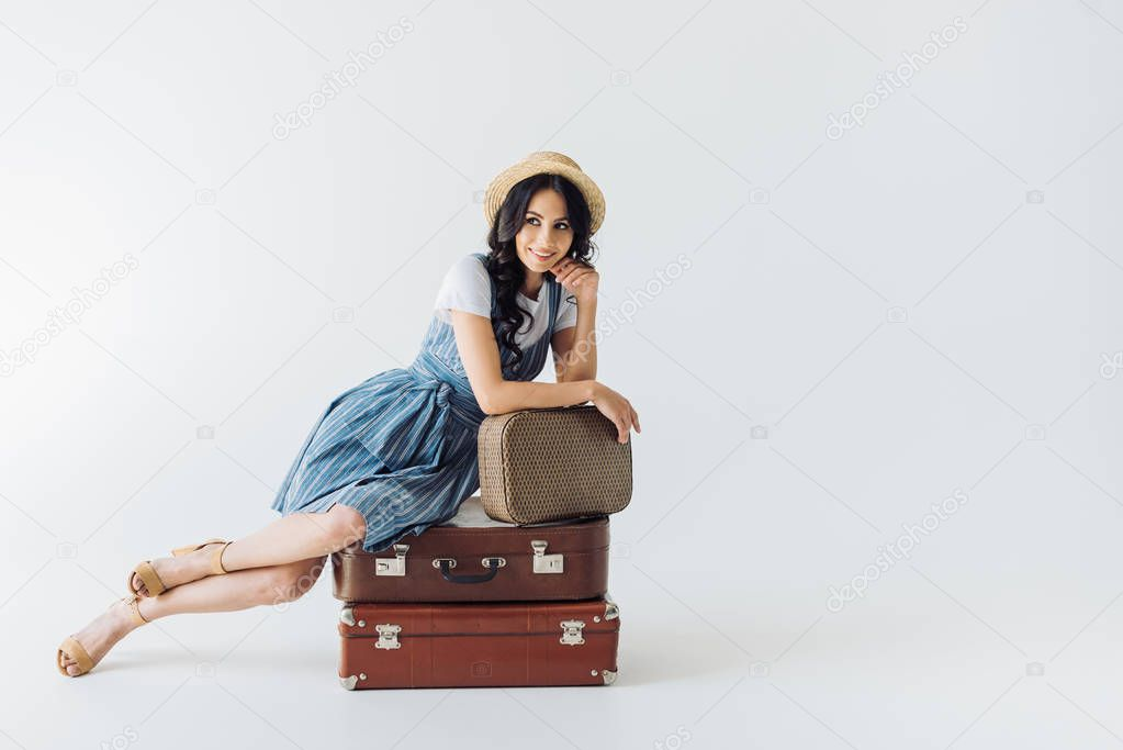 Smiling woman resting on luggage and looking away isolated on grey stock vector