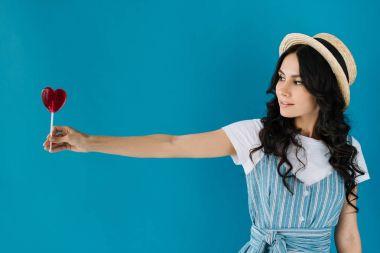 woman holding lollipop in hand
