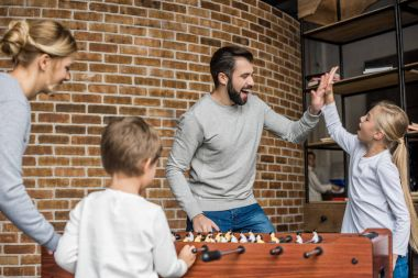 parents and kids playing table football