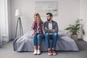 Photo argued couple sitting on bed