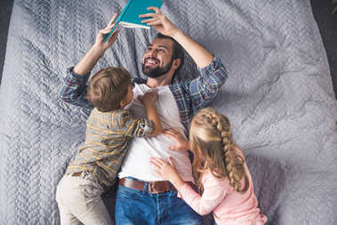father reading book to kids