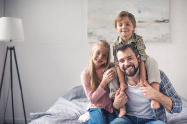 cheerful siblings and father