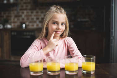 child with glasses of juice