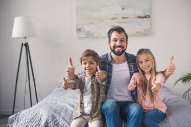 father and children showing thumbs up