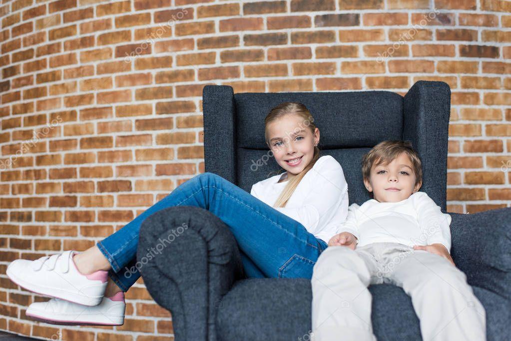 siblings resting on armchair