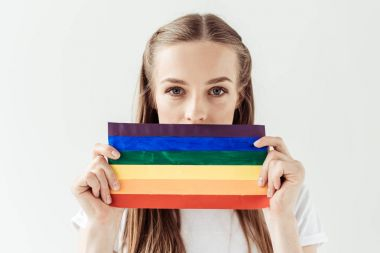 woman covering mouth with rainbow flag