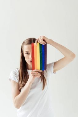 woman covering eye with rainbow flag
