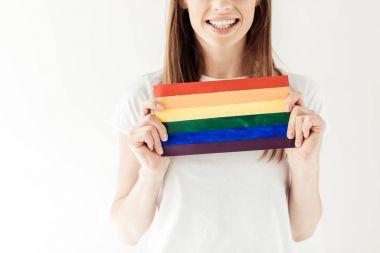 woman holding small rainbow flag