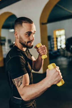 sportsman training with dumbbells