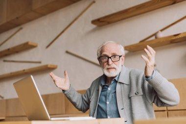 bewildered senior man with laptop