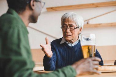 senior friends having discussion at bar